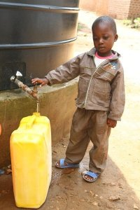A Ugandan boy fills a jug with clean water